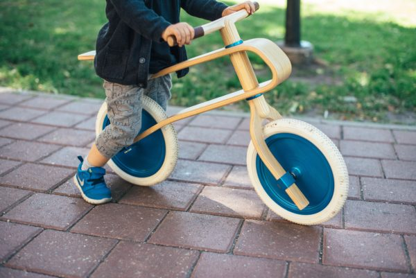 a little kid riding a balance bike